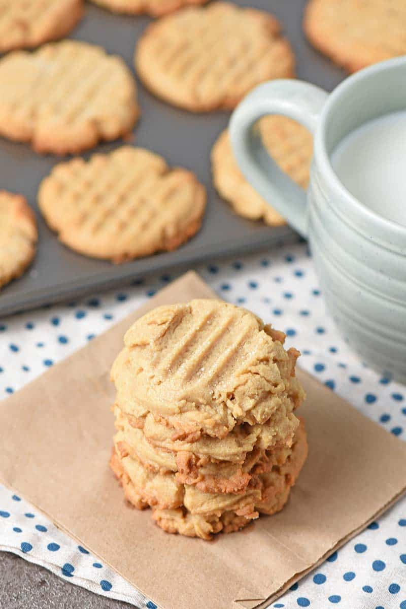 Stack of chewy peanut butter cookies on a paper bag with a cup of milk