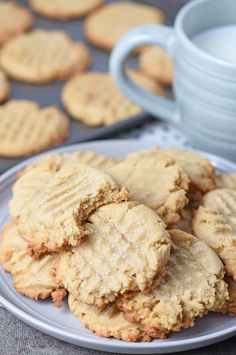 Chewy peanut butter cookies on a plate with a cup of milk