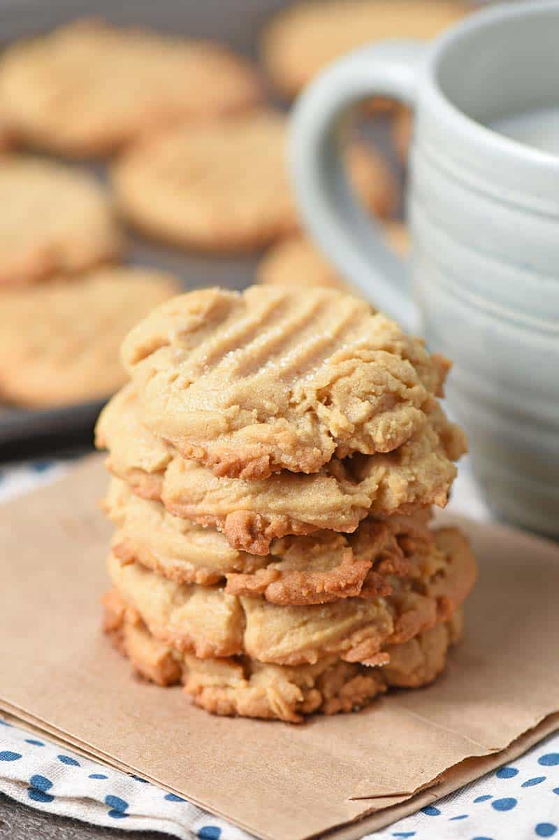 Stack of chewy peanut butter cookies on a brown paper bag with a cup of ice cold milk
