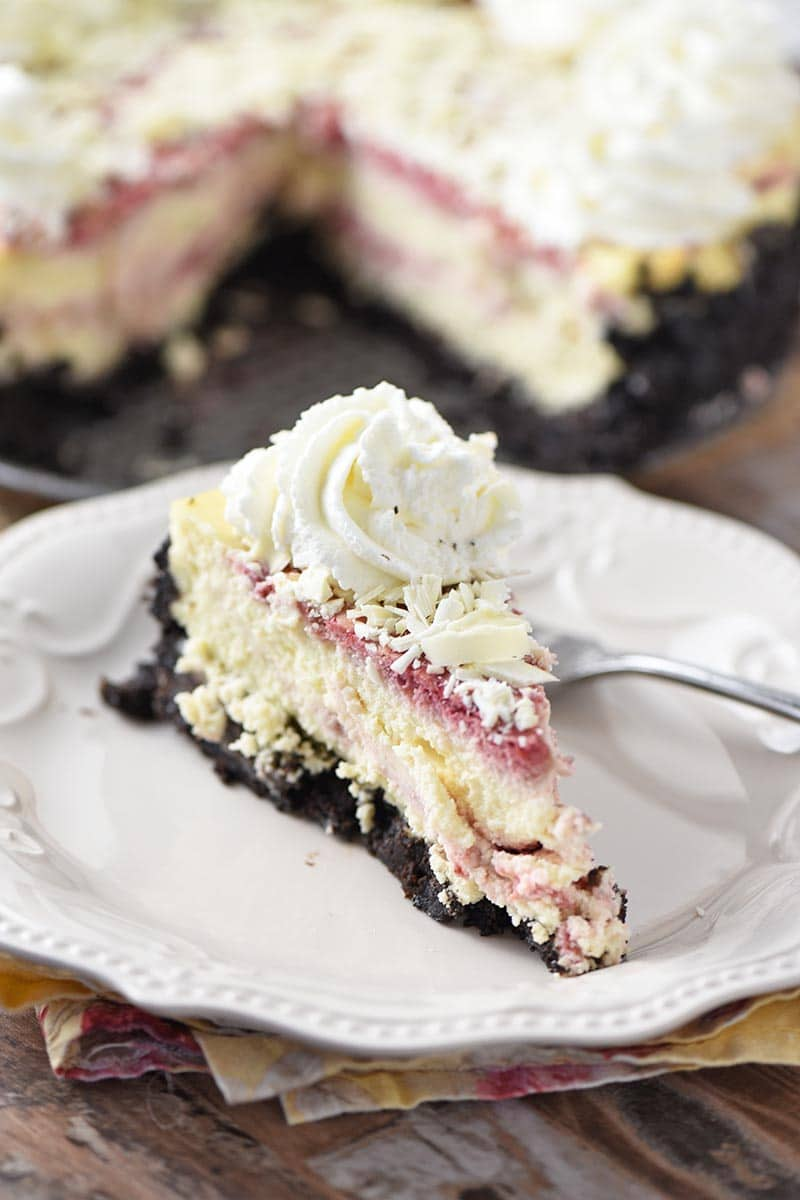 slice of raspberry swirl cheesecake with white chocolate and whipped cream on white plate