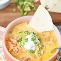 orange Fire-King soup bowl with chicken enchilada soup, tortilla triangle, sour cream, and green onions