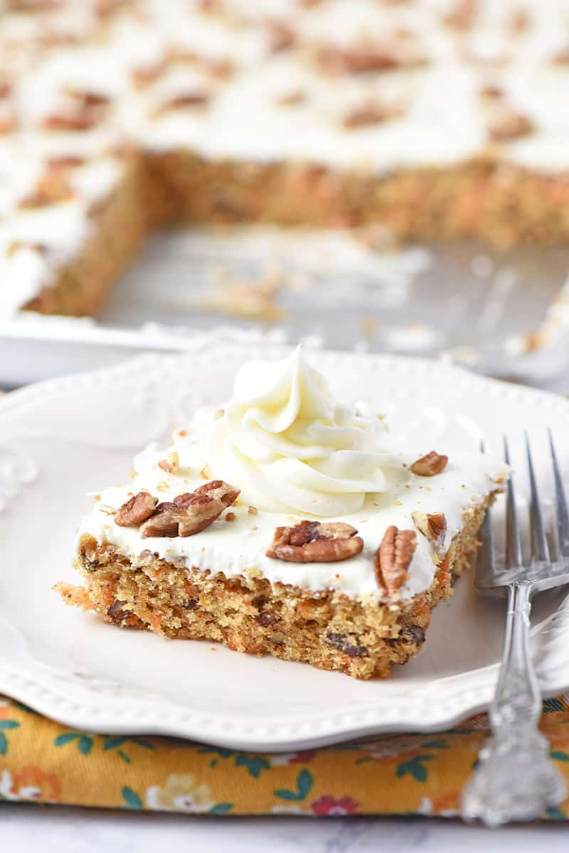 slice of the best ever carrot cake with a swirl of cream cheese frosting on top