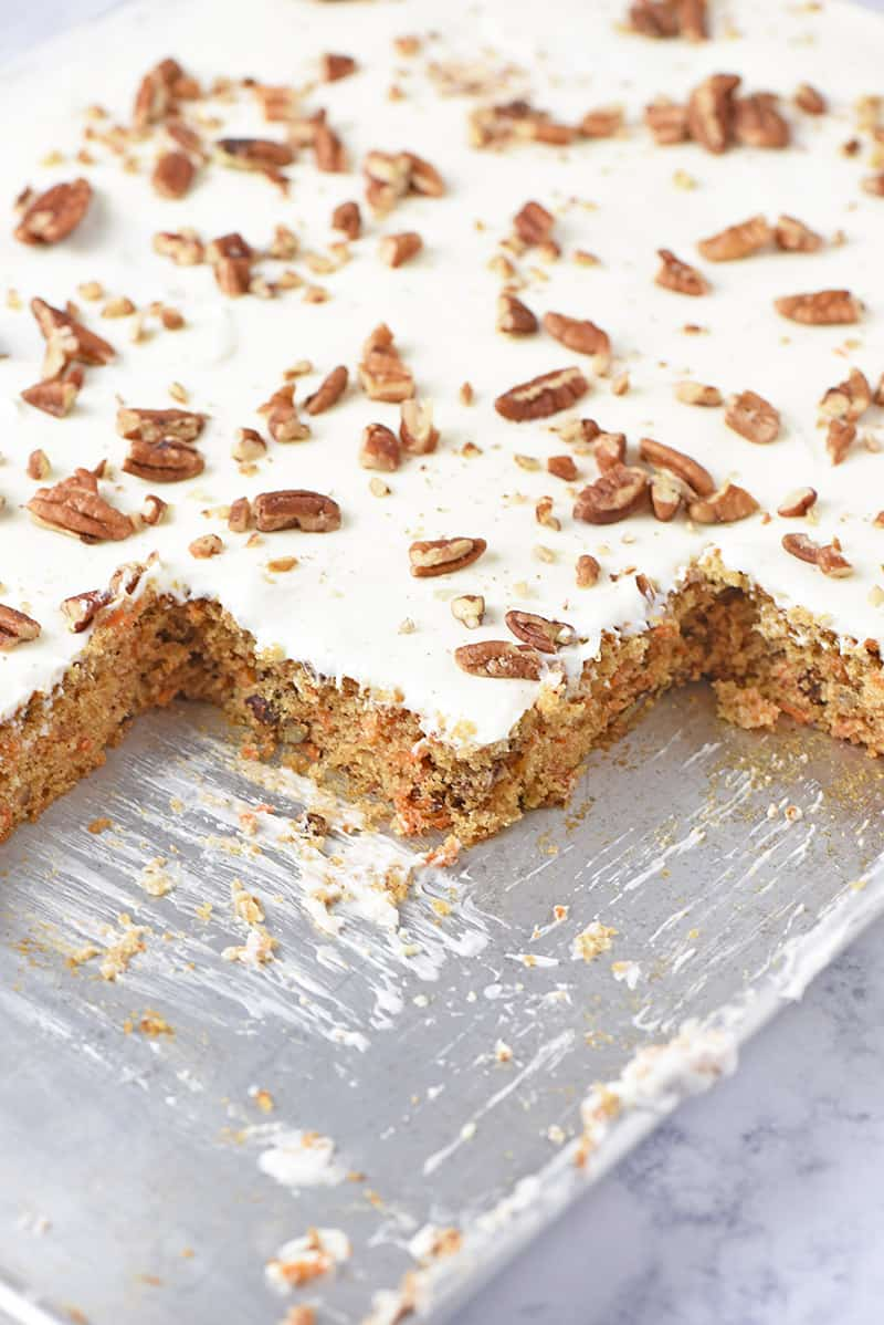carrot cake from scratch in a sheet pan with cream cheese frosting and pecans on top