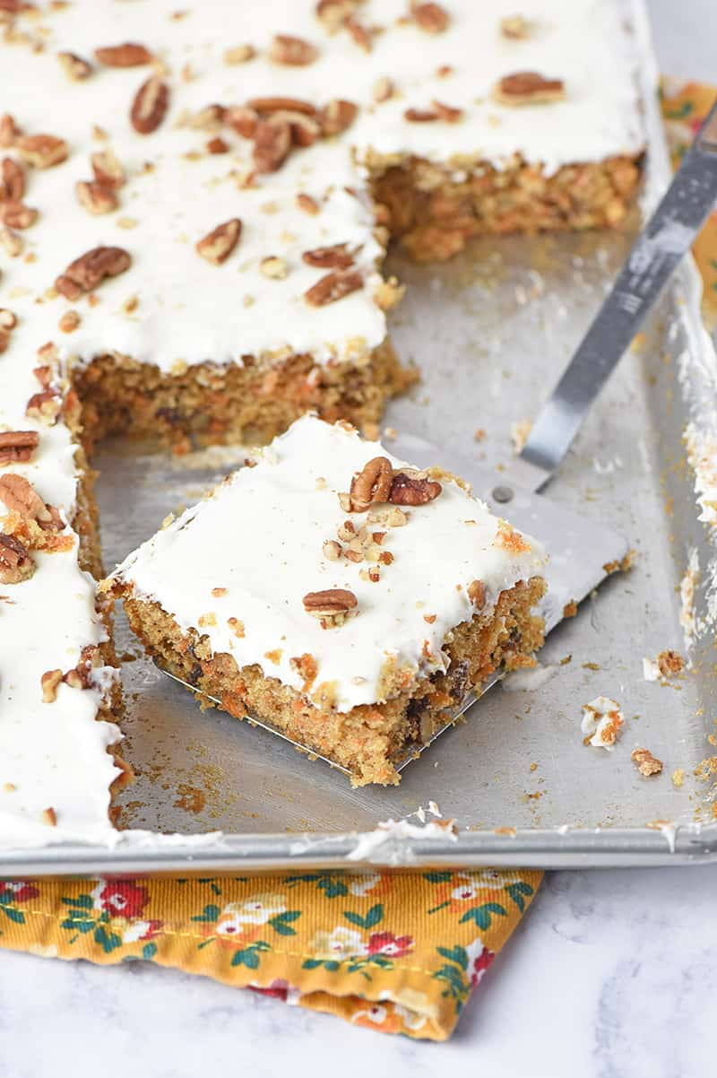 easy carrot cake recipe sliced on a spatula in a sheet pan