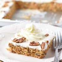 cream cheese frosting swirl on slice of carrot cake on white plate with fork