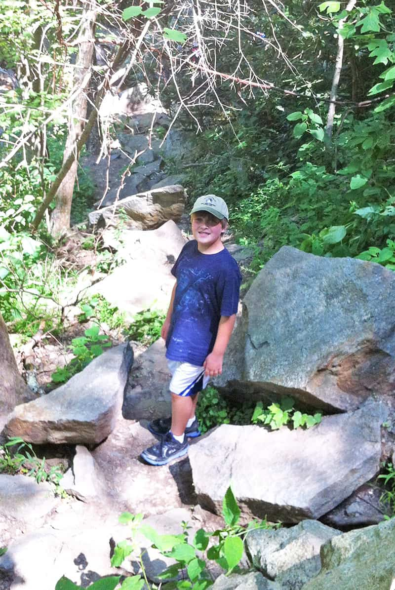 Boy climbing on rocks around Laurel Falls Trail in Smoky Mountains, Tennessee