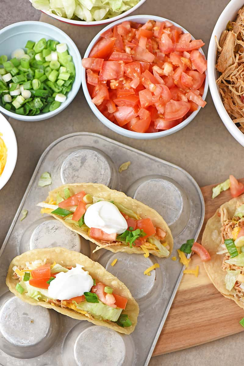 shredded chicken tacos with fresh ingredients on a muffin pan
