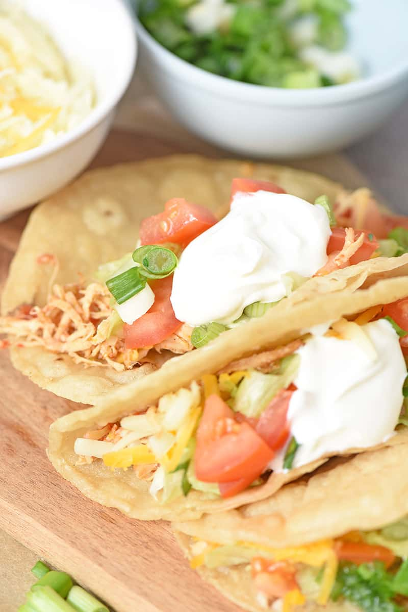 easy chicken tacos on a cutting board close up with fresh ingredients and sour cream