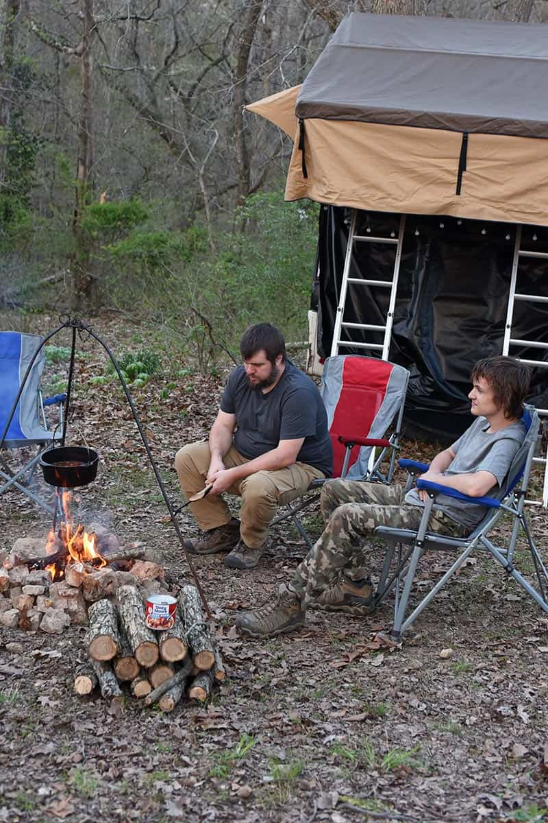 dad and son enjoying campfire cooking and rooftop tent camping