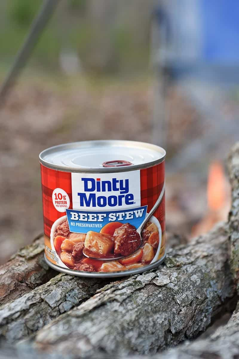 can of DINTY MOORE® Beef Stew with campfire in background
