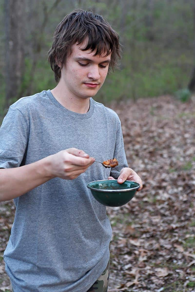 boy taking bite of beef stew with camping cooking gear like real bowls and eating utensils