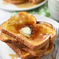 French toast on a plate with butter and maple syrup and a mug of milk