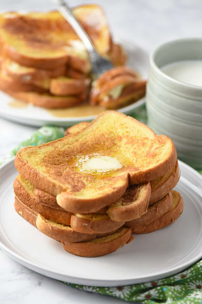 pile of French toast on plate with mug of milk