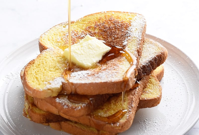 Pile of the best French toast recipe with butter and maple syrup, pouring syrup on