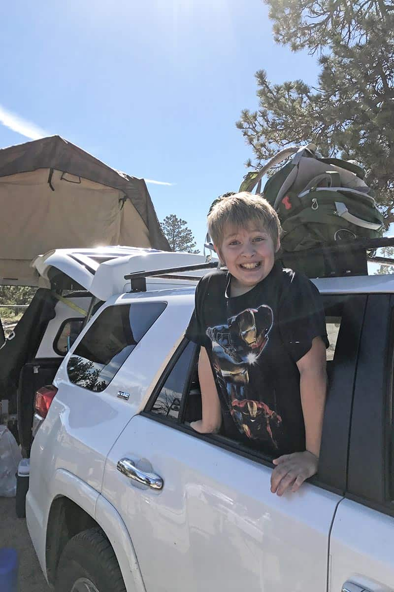 boy in white Toyota 4Runner packed up and ready to go camping with all the camping essentials