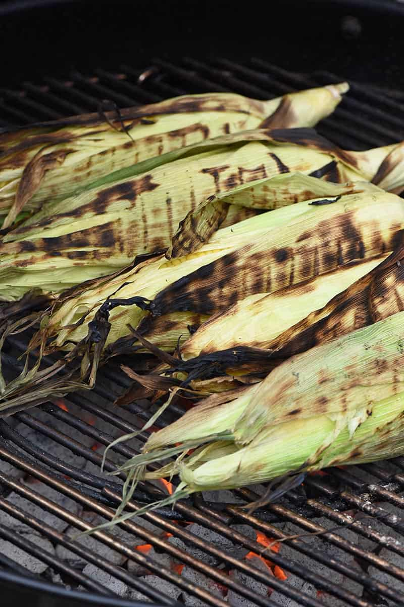 blackened grilled corn in the husk on a charcoal grill