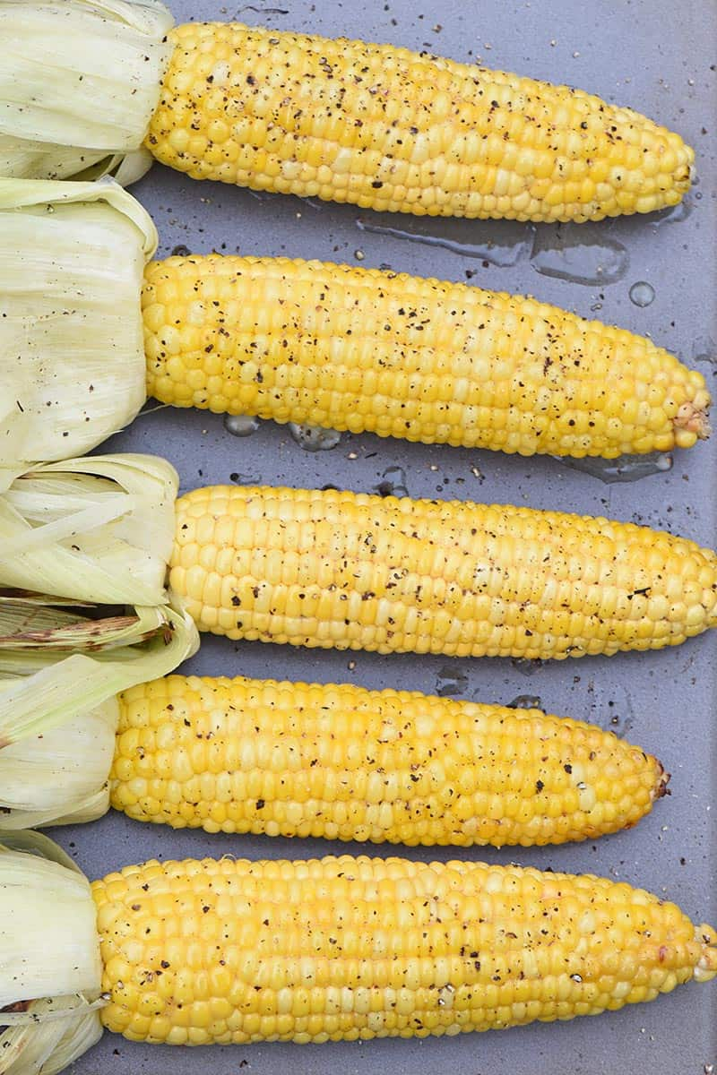 grilled corn in the husk on a cookie sheet with husks removed, seasoned with honey butter, salt, and pepper