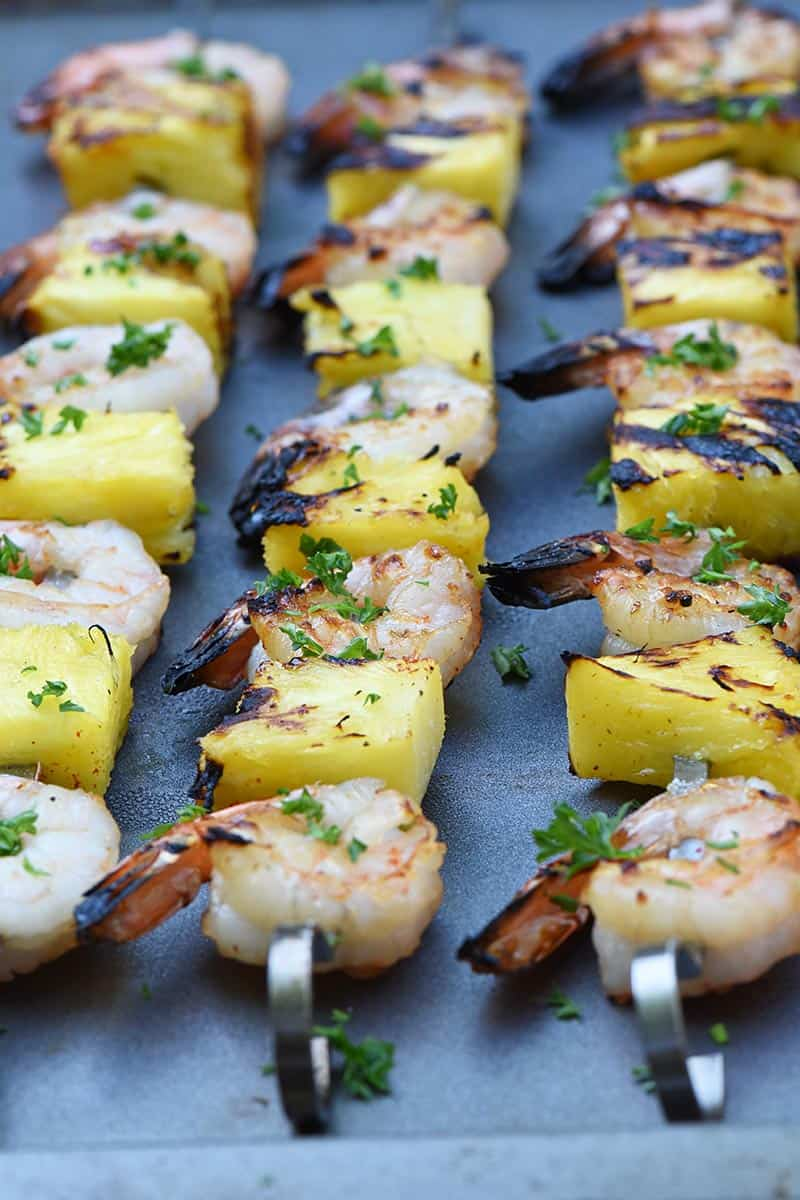 up close shrimp kabobs with pineapple grilled and placed on a cookie sheet
