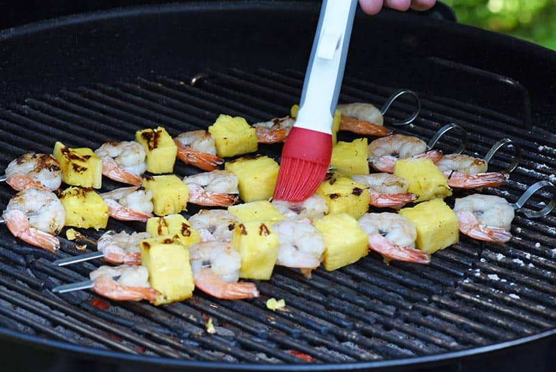 brushing a maple bourbon grilled shrimp marinade or glaze on shrimp kabobs on the charcoal grill