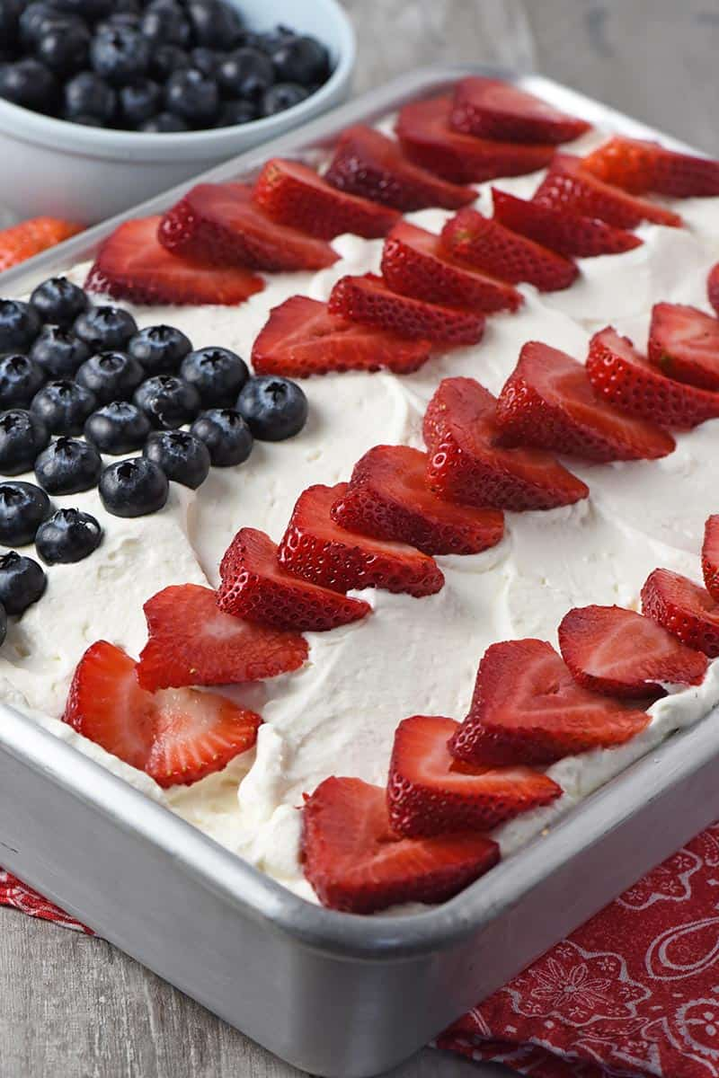 flag cake up close with fresh berries and whipped cream on top