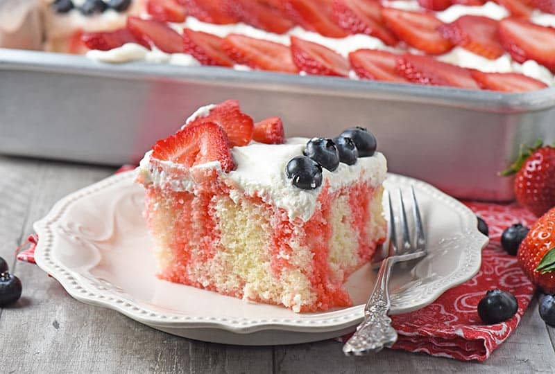 Slice of strawberry Jello poke cake on an ivory Pioneer Woman plate