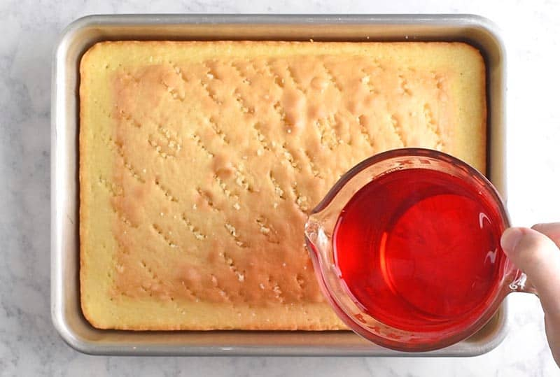 Pour strawberry Jello all over the top of a French vanilla poke cake for an easy 4th of July dessert.