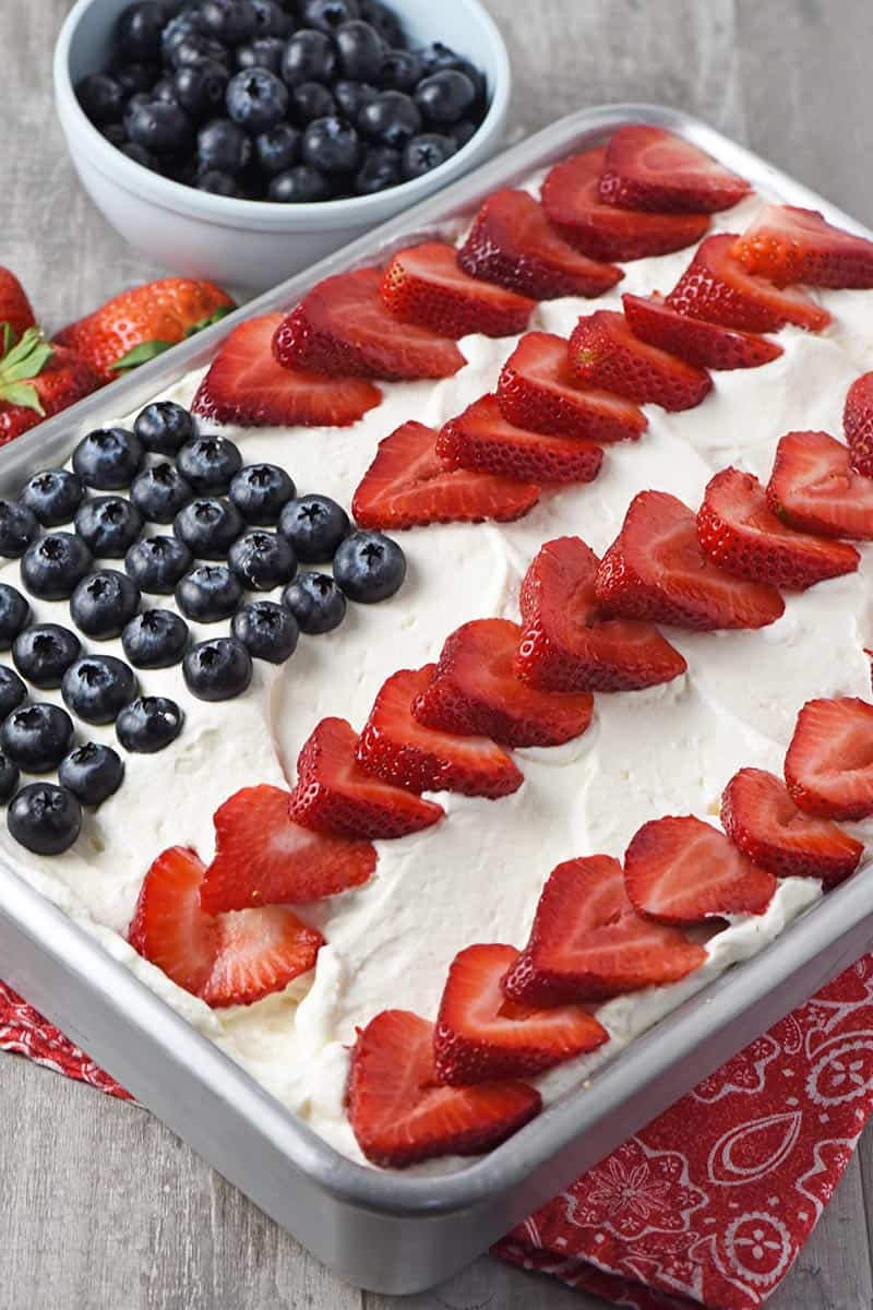 American flag cake decorated with whipped cream, blueberries, and strawberries