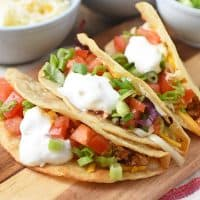 ground beef tacos with all the toppings on a wooden cutting board