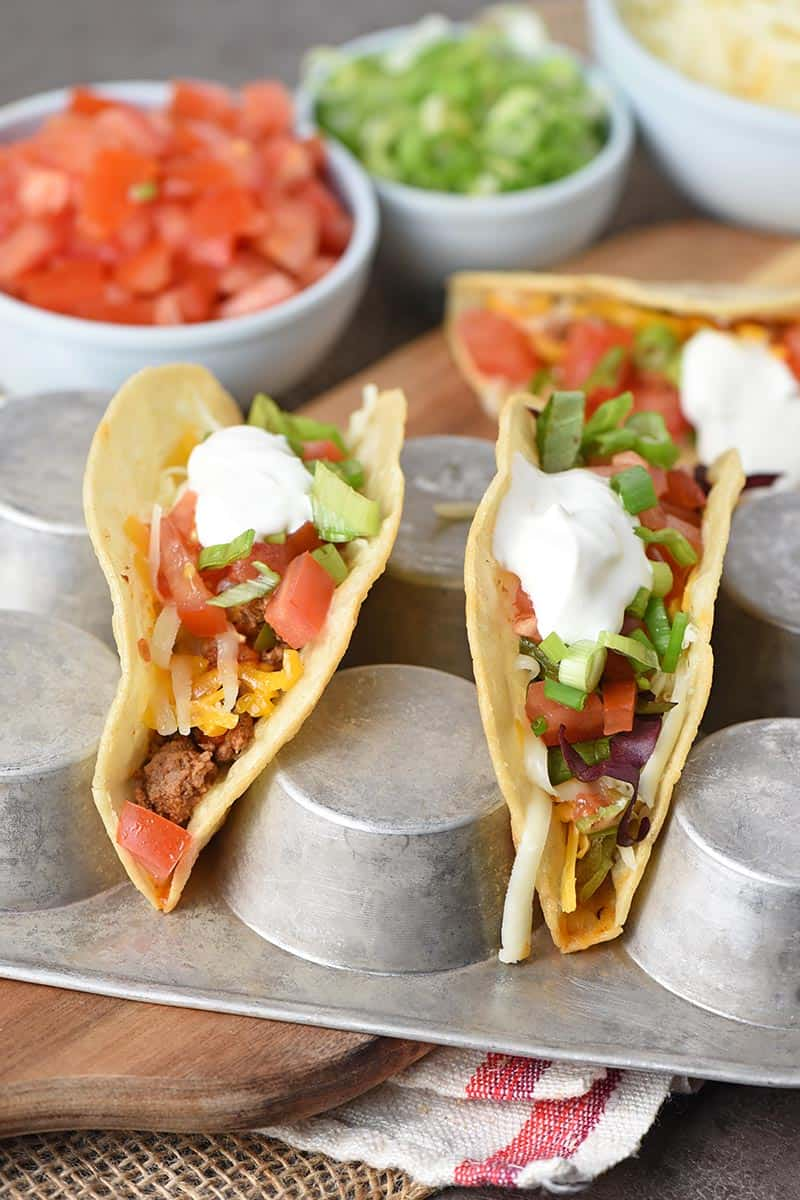 beef tacos in corn tortilla taco shells set in a muffin pan for filling with all the toppings