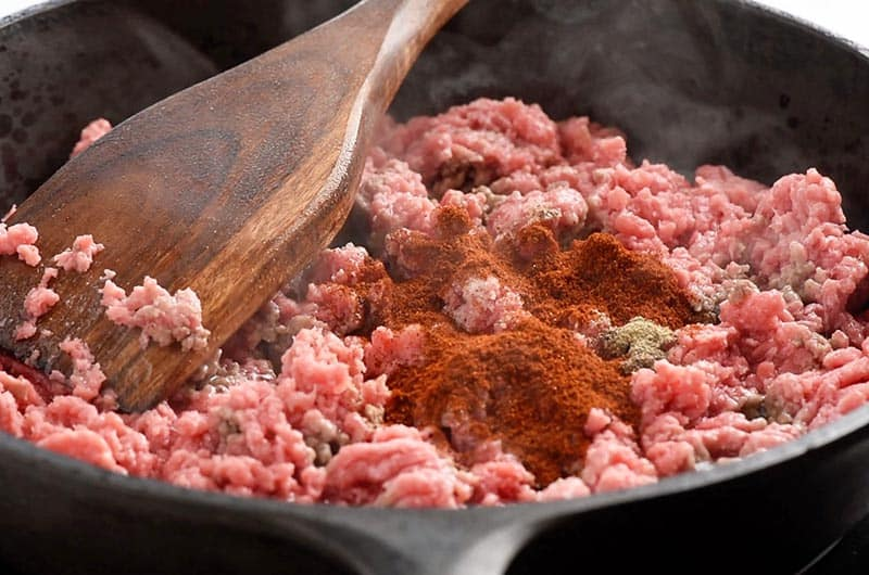cooking ground beef and seasoning for tacos in cast iron skillet