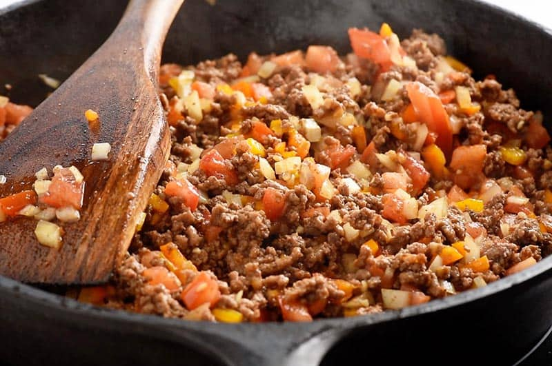 cooking ground beef with onion, peppers, and tomatoes in a cast iron skillet for a delicious taco recipe
