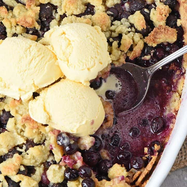 easy blueberry cobbler recipe in a baking dish with vanilla ice cream