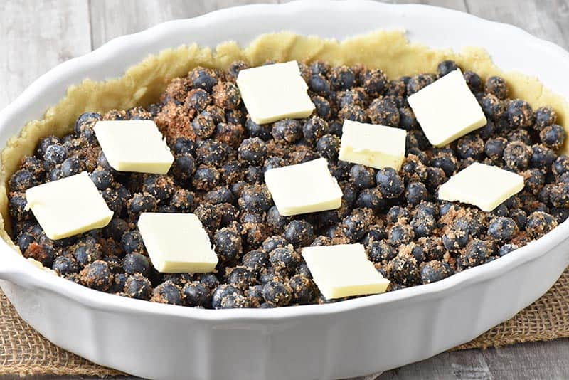 butter slices on top of blueberry cobbler in white baking dish