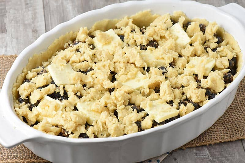 crumbled crust on top of blueberry cobbler in white baking dish