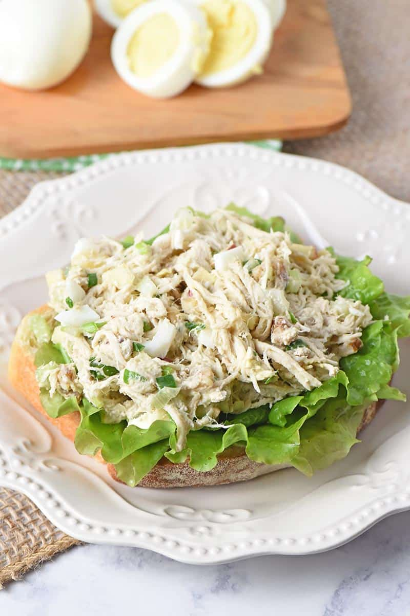 open-faced chicken salad sandwich on a plate with hard boiled eggs on a small wooden cutting board