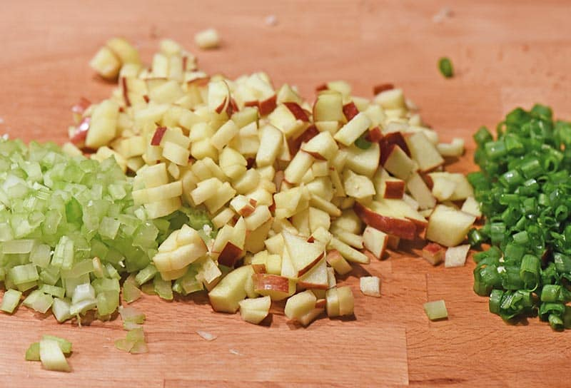 chopped celery, apples, and green onions on wooden cutting board for chicken salad sandwich