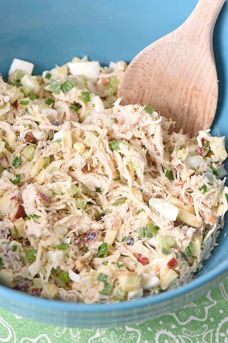 easy chicken salad recipe mixed up in a blue bowl with a wooden spoon
