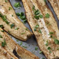 grilled fish fillets with cilantro on a baking sheet