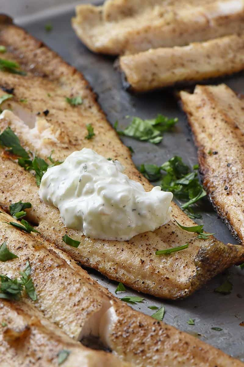 grilled fish fillets with a dollop of tzatziki sauce