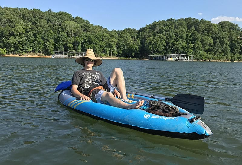 teen boy relaxing on inflatable kayak on Beaver Lake in Northwest Arkansas