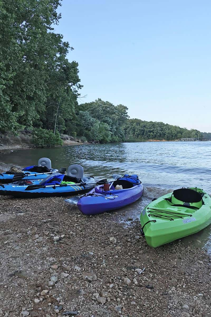 Sun Dolphin hardshell and Sevylor inflatable kayaks on beach of Beaver Lake in Northwest Arkansas