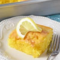 slice of lemon cake on white plate with slice of lemon on top
