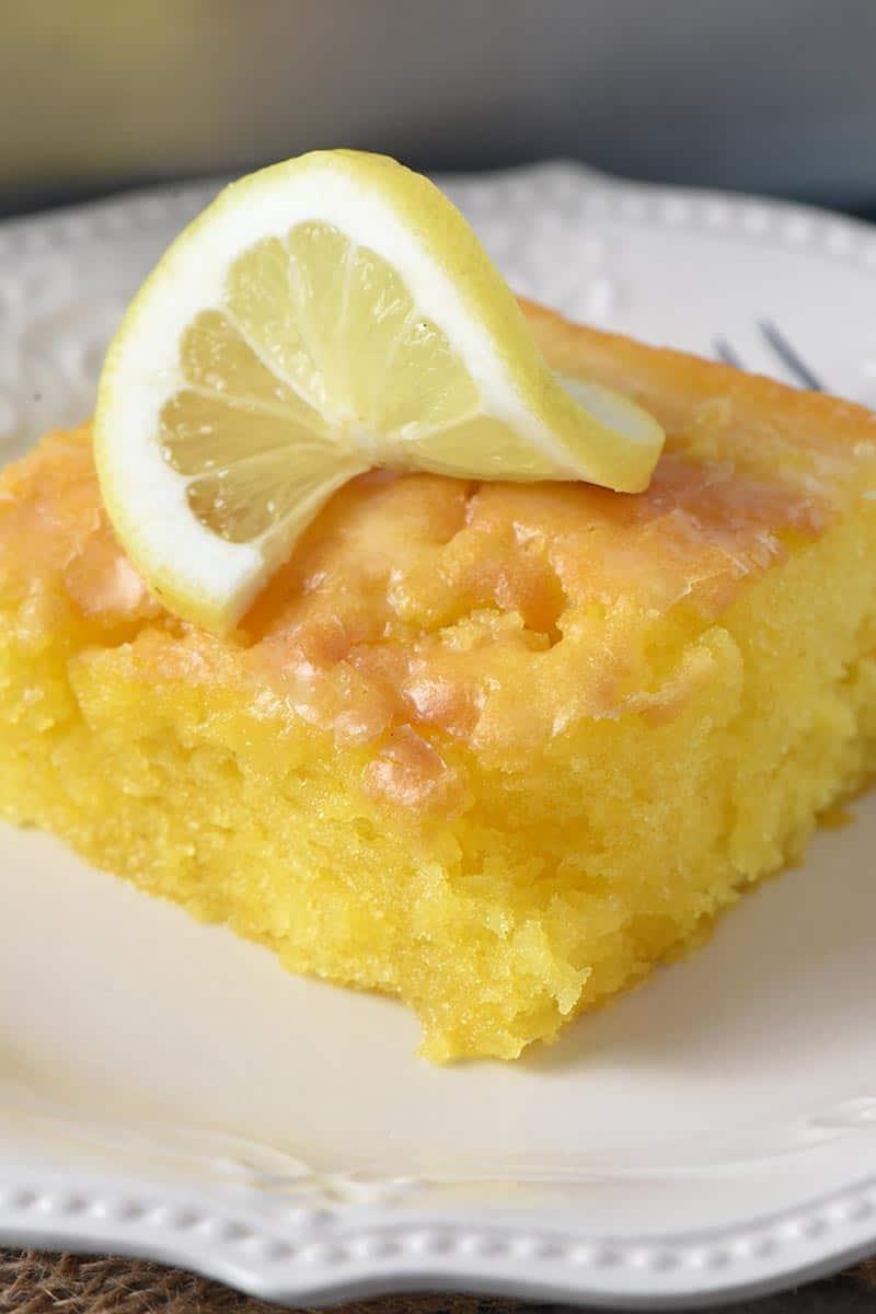 close up slice of lemon pudding cake with slightly crispy lemon glaze and slice of lemon on white plate