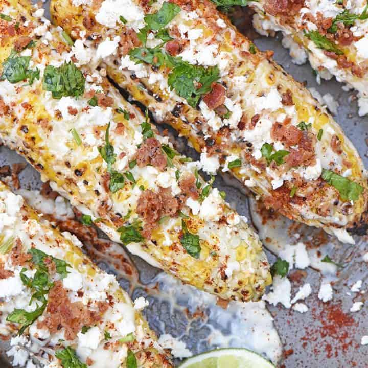 Mexican corn on a baking sheet with mayo, feta cheese, cilantro, bacon, and lime wedges