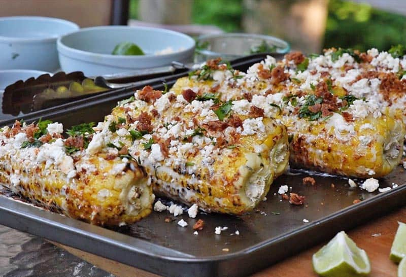 Mexican corn on the cob on a baking sheet