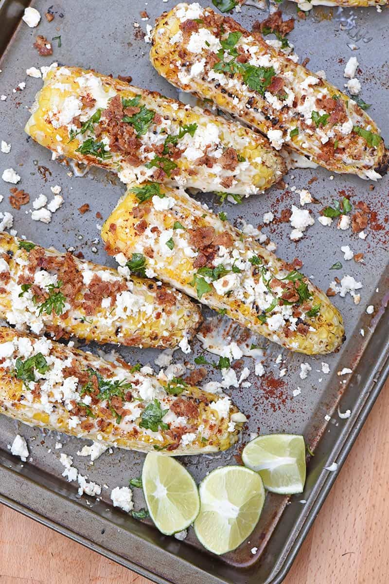 grilled Mexican corn on baking sheet with lime wedges and bacon crumbles