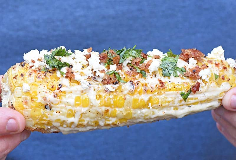 Grilled ear of Mexican corn on the cob with all the fixings, including mayo, Feta cheese, cilantro, and bacon