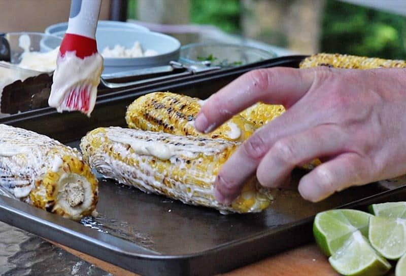 brushing mayo onto ears of grilled corn with basting brush for mexican street corn recipe