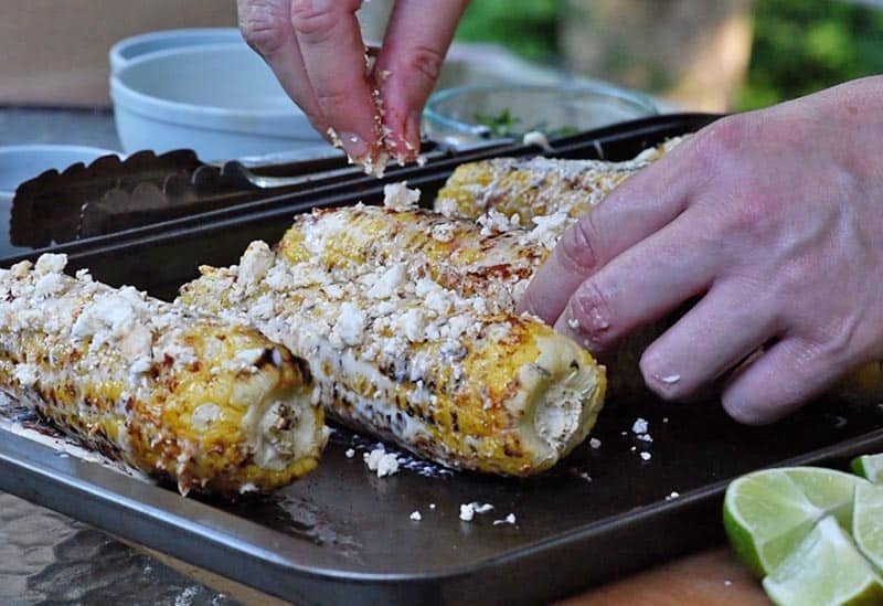 crumbling Feta cheese onto grilled corn on the cob for Mexican corn recipe