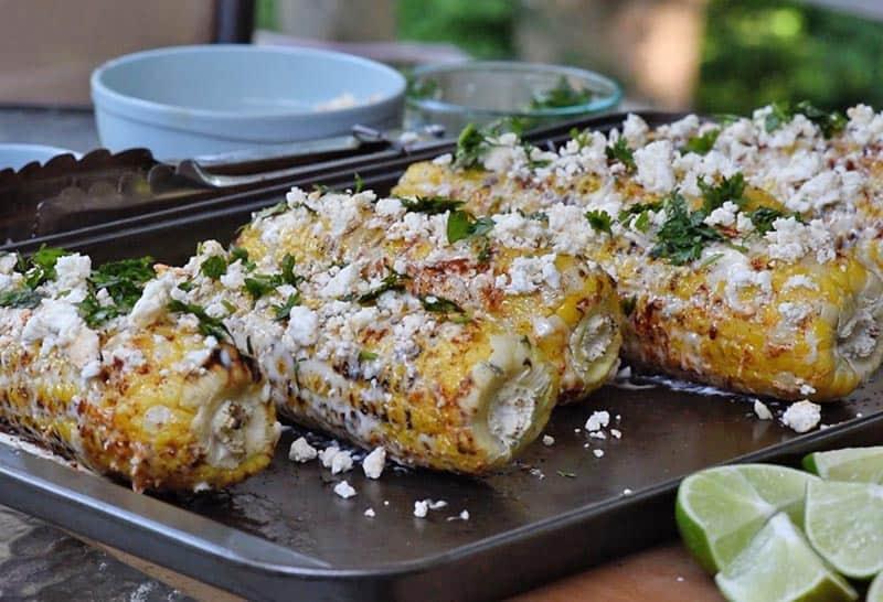 adding cilantro to mexican corn on the cob